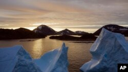 An aerial view of large Icebergs floating as the sun rises near Kulusuk, Greenland, early Aug. 16, 2019.
