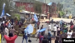 FILE - A still image taken from a video shot on October 1, 2017, shows protesters waving Ambazonian flags in front of road block in the English-speaking city of Bamenda, Cameroon.