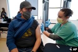 Brian Kennedy (kiri), guru olahraga di SD Green Valley menerima suntikan vaksin COVID-19 untuk karyawan Sekolah Negeri Denver, di Denver.