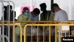 Medical personnel sort out medical supplies at a dormitory during the coronavirus disease (COVID-19) outbreak in Singapore, April 20, 2020.
