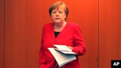 German Chancellor Angela Merkel waits for the beginning of a press conference in Berlin, Germany, May 6, 2020 after an online meeting of Merkel and the German state governors on the loosening of the restictions to reduce the spread of the new coronavirus.