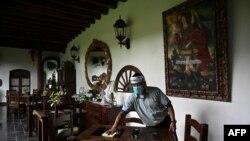 Un hombre limpia una mesa en el área de restaurante de un hotel en Antigua Guatemala, departamento de Sacatepéquez, a 45 km al sureste de la ciudad de Guatemala el 6 de septiembre de 2020.
