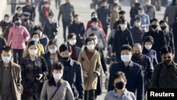 People wearing protective face masks commute amid concerns over the new coronavirus disease (COVID-19) in Pyongyang, North Korea, March 30, 2020, in this photo released by Kyodo.