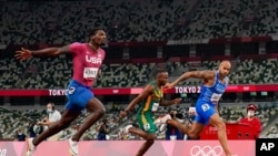 Lamont Jacobs, right, of Italy, wins the men's the 100-meter final at the 2020 Summer Olympics, Aug. 1, 2021, in Tokyo.
