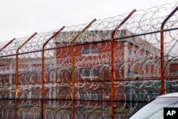 FILE - In this March 16, 2011, file photo, a security fence surrounds inmate housing on the Rikers Island correctional facility in New York.