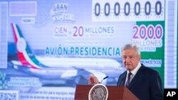 Presiden Andres Manuel Lopez Obrador berdiri di depan gambar tiket undian yang menampilkan pesawat kepresidenan, dalam konferensi pers pagi di Istana Nasional di Meksiko. (Foto: Kantor Pers Presiden Meksiko via AP)