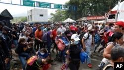 Para migran mencoba melintasi perbatasan dari Corinto, Honduras, ke Corinto, Guatemala, 1 Oktober 2020. (Foto: AP)