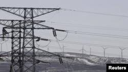 Torres eléctricas y turbinas de viento de la corporacion china State Grid se observan en una foto en la provincia de Hebei.