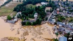 A damaged castle, left, is seen in Erftstadt-Blessem, Germany, July 17, 2021.