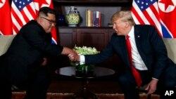 지난 2018년 6월 12일 싱가포르에서 열린 첫 미-북 정상회담에서 도널드 트럼프 미국 대통령과 김정은 북한 국무위원장이 악수하고 있다.