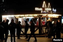 People stand around a mulled wine to-go stand at a Christmas market at Breitscheidplatz square, amid the COVID-19 pandemic in Berlin, Germany, Dec.10, 2020.