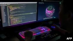 """一名化名为王子的中国黑客是""""红色黑客联盟""""成员,在广东东莞的办公室里监察全球网络攻击。(2020年8月4日)"""