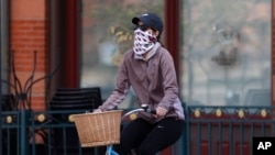 A bicyclist wears face protection against the new coronavirus while pedaling through Larimer Square early Saturday, April 25, 2020, in downtown Denver.