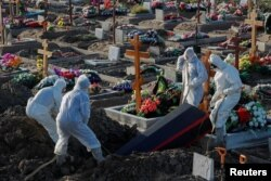 Rusya'nın St. Petersburg şehrinde görevliler koruyucu giysiler içerisinde COVID-19 nedeniyle ölenleri defnediyorlar.