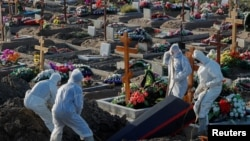 Grave diggers wearing personal protective equipment (PPE) lower a coffin while burying a person in the special purpose section of a graveyard for the coronavirus disease (COVID-19) victims on the outskirts of Saint Petersburg, Russia, Nov. 6, 2020.