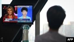 ຜູ້ດຳເນີນລາຍການ ລຸຍ ຊິນ ຂອງໂທລະພາບ CGTN ທີ່ຈີນເປັນເຈົ້າຂອງ ແນມເບິງຈໍພາບ ທີ່ສະແດງໃຫ້ເຫັນ ຜູ້ກ່ຽວກຳລັງໂຕ້ວາທີ ກັບຜູ້ນຳສະເໜີ ທຣິດສ໌ ເຣແກັນ ຂອງໂທລະພາບ Fox Business Network ຢູ່ທີ່ສຳນັກງານໃຫຍ່ ຂອງ CCTV ໃນປັກກິ່ງ ເມື່ອວັນທີ 30 ພຶດສະພາ 2019.