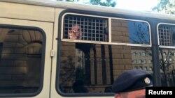 Arhiva - Policajac stoji ispred autobusa sa novinarima uhapšenim tokom mitinga u Moskvi, 7. jula 2019.