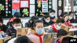 Elementary school students wearing face masks attend a class as they return to school after the start of the term was delayed due to the COVID-19 coronavirus outbreak, in Huaian in China's eastern Jiangsu province on April 7, 2020. (Photo by STR /…
