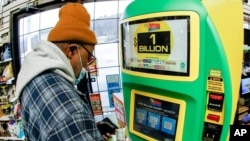 A patron uses the kiosk at a Smoker Friendly store to purchase tickets for the Mega Millions lottery drawing, Jan. 22, 2021, in Cranberry Township, Pa. A player in Michigan bought the winning ticket for the $1.05 billion jackpot.