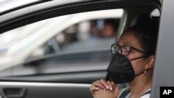 Una mujer que usa una máscara para frenar la propagación del nuevo coronavirus, asiste a una misa en autocine en Chia, Colombia, el domingo 30 de agosto de 2020.