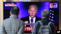 People watch a TV screen showing the broadcast of President-elect Joe Biden speaking, at the Seoul Railway Station in Seoul, South Korea, Sunday, Nov. 8, 2020. (AP Photo/Ahn Young-joon)