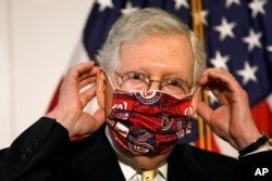 FILE - Senate Majority Leader Mitch McConnell of Kentucky puts on a face mask on Capitol Hill in Washington, July 21, 2020, .
