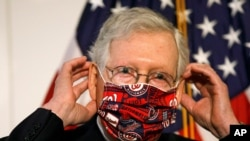Senate Majority Leader Mitch McConnell of Ky., puts a face mask on after speaking at news conference after attending a Republican luncheon, July 21, 2020, on Capitol Hill in Washington.
