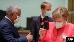 António Costa (e), primeiro-ministro de Portugal, oferece um presente a chanceler alemã, Angela Merkel( d), num dos intervalos da cimeira de Bruxelas.