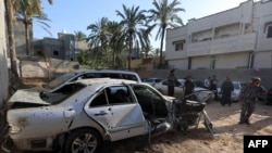 FILE - Libyans check the site of shelling north of the Libyan capital, Tripoli, April 17, 2020.