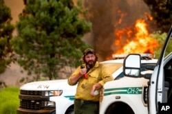 U.S. Forest Service firefighter Chris Voelker monitors the Sugar Fire, part of the Beckwourth Complex Fire, burning in Plumas National Forest, Calif., July 9, 2021.