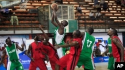 FILE - A player from Kano Pillars, center, in green and white, jumps to make a basket, challenged by Mark Mentors players in red and black, during Nigeria's Final Four in Lagos, Nigeria, Sept. 5, 2013.