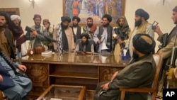 FILE - Taliban fighters take control of the Afghan presidential palace after President Ashraf Ghani fled the country, in Kabul, Afghanistan, Aug. 15, 2021.