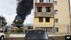 ຮູສະເກັດຂອງລະເບີດໃນລົດຄັນນຶ່ງ ໃນຂະນະທີ່ ຕຶກອາຄານກຳລັງຖືກໄຟໄໝ້ຢູ່ດ້ານຫລັງ ຫຼັງຈາກທີ່ ຖືກຍິງຖະລົ່ມໂດຍປືນໃຫຍ່ຂອງອາເຈີບາຍຈານ ໃນລະຫວ່າງການຕໍ່ສູ້ທາງທະຫານ ໃນການປະກາດເປັນເຂດສາທາລະນະລັດ Nagorno-Karabakh, Stepanakert, ໃນວັນອາທິດ ທີ 4, ຕຸລາ 2020.
