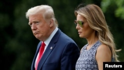 FILE - U.S. President Donald Trump and first lady Melania Trump walk to the Marine One helicopter from the South Lawn of the White House in Washington, May 27, 2020.
