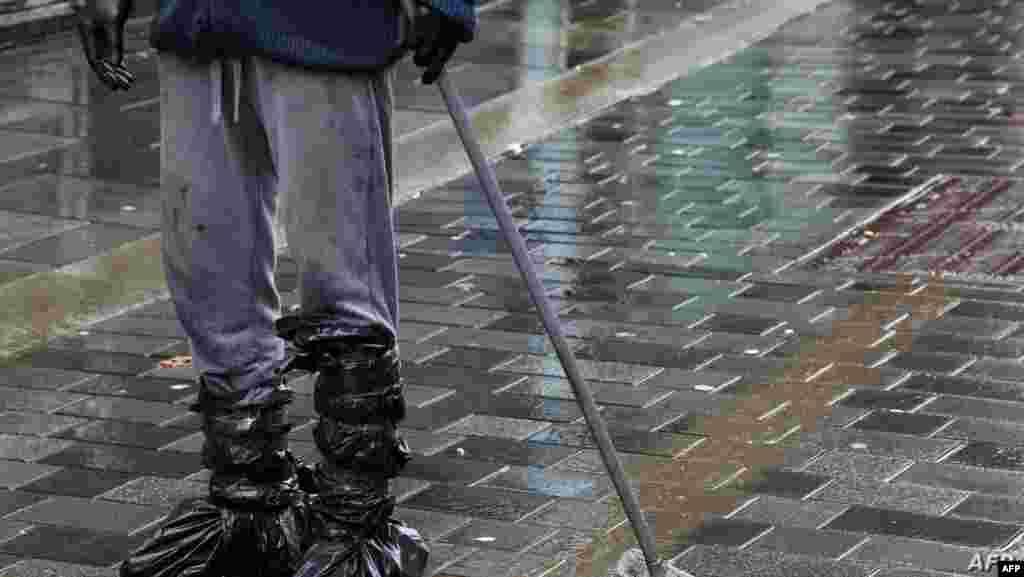 폭풍 '데니스'가 휩쓸고 간 영국 사우스웨일스에서 쓰레기 봉투로 발을 감싼 남성이 거리에 남은 진흙을 쓸어내고 있다.