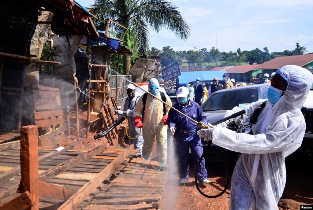 Des responsables sanitaires ougandais désinfectent le marché en plein air de Nakawa dans le cadre des mesures visant à prévenir la propagation de la maladie à coronavirus dans la division de Nakawa à Kampala, le 17 avril 2020.