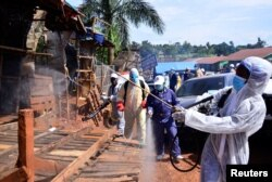 FILE - Ugandan health officials wearing protective gear disinfect the Nakawa open-air market as part of the measures to prevent the spread of the coronavirus disease (COVID-19), in Nakawa division of Kampala, April 17, 2020.