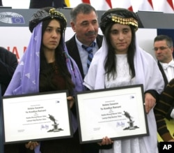 FILE - Yazidi women from Iraq, Nadia Murad Basee, left, and Lamiya Haji Bashar, pose with their award after receiving the European Union's Sakharov Prize for human rights at the European Parliament in Strasbourg, France, Dec. 13, 2016.