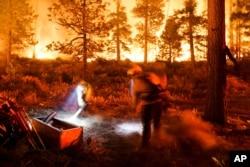 Dua petugas pemadam kebakaran berupaya memadamkan api Kebakaran Caldor di South Lake Tahoe, California, 30 Agustus 2021.