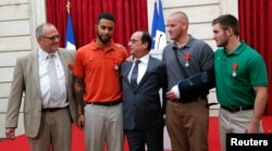 FILE - Then-French President ollande poses with British businessman Chris Norman, US student Anthony Sadler, US Airman First Class Spencer Stone and US National Guardsman Alek Skarlatos (R) during a ceremony at the Elysee Palace, Aug. 24, 2015.