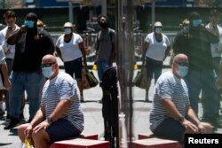 FILE - People wear masks to prevent the spread of coronavirus, as the delta variant has led to a surge in infections, in New York City, July 30, 2021.