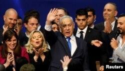 PM Israel Benjamin Netanyahu didampingi istrinya, Sara melambaikan tangan ke arah para pendukungnya di markas besar partai Likud di Tel Aviv, Israel, 3 Maret 2020. REUTERS/Amir Cohen