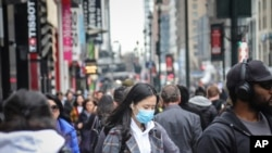 -A pedestrian wears a surgical mask on a busy street in mid-town Manhattan, as concerns grow around COVID-19, Tuesday March 3, 2020, in New York. A man from New York City's suburbs was hospitalized in serious condition with COVID-19 on Tuesday, a…