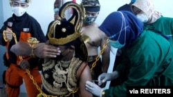 An Indonesian health care worker injects Sinovac's vaccine to a man dressed in Indonesia's traditional human puppet costume known as Wayang, as Indonesia drives mass vaccination for COVID-19, in Central Java province, Indonesia. (Antara Foto)