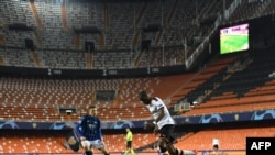FILE - This handout photograph released by UEFA March 10, 2020, shows Valencia CF and Atalanta players competing for the ball in a stadium without spectators due to coronacirus fears, at Estadio Mestalla, in Valencia, Spain.