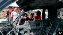 在巴格達薩德爾城一處熱鬧的露天舊家具市場外的爆炸現場,男孩查看一輛被炸毀汽車。(2021年4月15日)