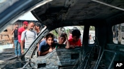 Boy look at a damaged vehicle at the scene of a powerful explosion at a crowded outdoor used furniture market in Sadr City neighborhood of Baghdad, Iraq, April 15, 2021.