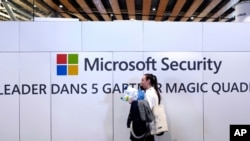 FILE - A woman walks in front of the Microsoft stand during the Cybersecurity Conference in Lille, northern France, Wednesday Jan. 29, 2020. Microsoft announced legal action Monday, Oct. 12, 2020 seeking to disrupt a major cybercrime digital network…