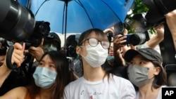 Agnes Chow, ao centro, destacada activista pró-democracia, senyenciada no ano passado pelo seu papel em protesto não autorizado , foi libertada no sábado, 12 de Junho de 2021, em Hong Kong