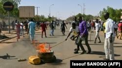 Les partisans de l'opposition nigérienne allument un feu et scandent des slogans alors qu'ils participent à une manifestation dans les rues de Niamey, le 23 février 2021.